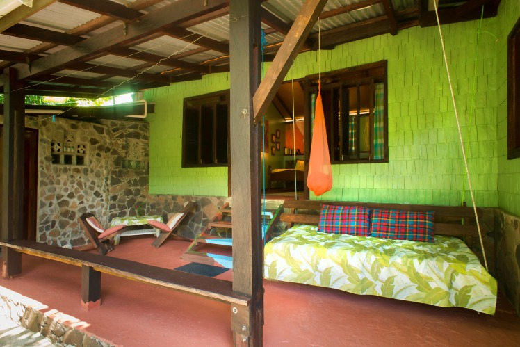 A mosquito net hangs to protect you should you need it. The fabrics and colours reflect the rainforest and the cocoa