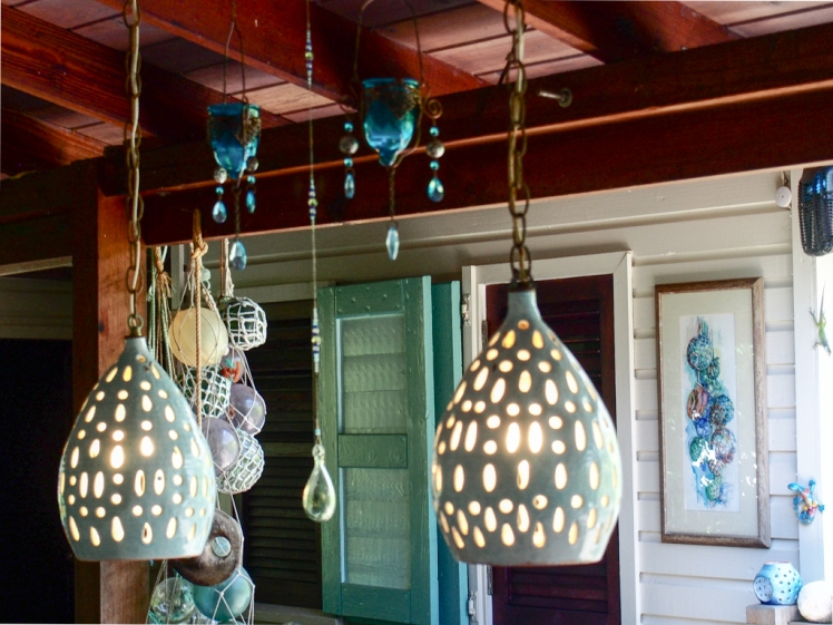 Sarah Fuller Pottery lights in her Caribbean home. Art by Jan Fararra. Fishing floats discovered beachcombing. Photo by Jennifer Ritchie.